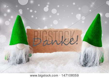 Christmas Greeting Card With Two Green Gnomes. Sparkling Bokeh And Noble Silver Background With Snow. German Text Danke Means Thank You