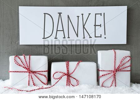 Label With German Text Danke Means Thank You. Three Christmas Gifts Or Presents On Snow. Cement Wall As Background. Modern And Urban Style. Card For Birthday Or Seasons Greetings.