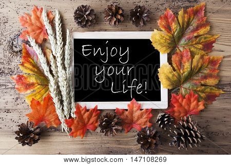 Blackboard With Autumn Or Fall Decoration. Greeting Card For Seasons Greetings. Colorful Leaves, Fir Cone And Barley On Aged Wooden Background. English Quote Enjoy Your Life