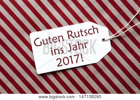 One Label On A Red And Brown Striped Wrapping Paper. Textured Background. Tag With Ribbon. German Text Guten Rutsch Ins Jahr 2017 Means Happy New Year