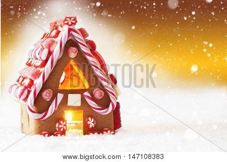 Gingerbread House In Snow As Christmas Decoration. Candlelight For Romantic Atmosphere. Copy Space For Advertisement. Golden Background With Snowflakes