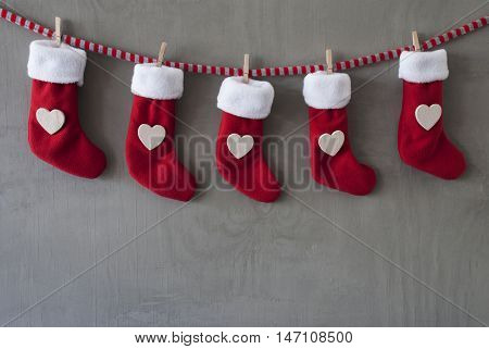 Nicholas Boots As Advent Calendar Hanging On A Line. Cement Wall As Modern Background. Textile Shoes With Hearts.