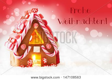 Gingerbread House In Snowy Scenery As Christmas Decoration. Candlelight For Romantic Atmosphere. Red Background With Bokeh Effect. German Text Frohe Weihnachten Means Merry Christmas