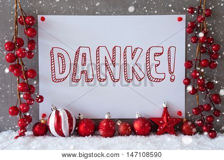 Label With German Text Danke Means Thank You. Red Christmas Decoration Like Balls On Snow. Urban And Modern Cement Wall As Background With Snowflakes.