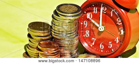 Alarm clock and money coins. Time is money concept.