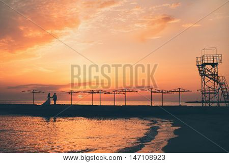 Silhouette of couple on pier at sunset. Date night