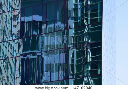 Highrise building with modern windows which is showing reflections of the cityscape