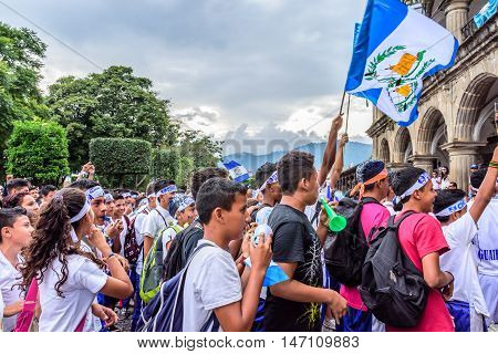 Antigua Guatemala - September 14 2015: Locals wave Guatemalan flags & cheer outside city hall during Guatemalan Independence Day celebrations