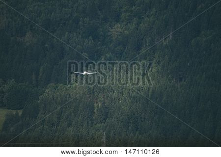 Small plane flies over the dense green forest. Travel concept with space for text or advertisement