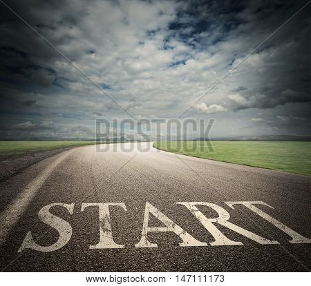 Word start written on asphalt road with field landscape