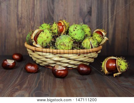 chestnuts in a wattled basket on a wooden background