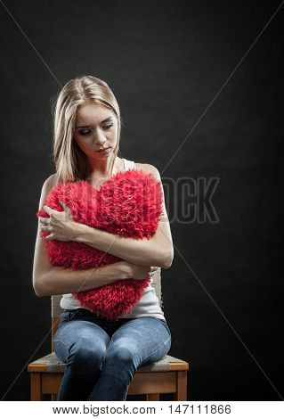 Broken heart love concept. Sad unhappy woman holding red heart pillow dark background