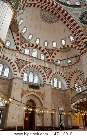 Istanbul, Turkey - November 5, 2015. Interior of Shehzade Mehmet mosque in Istanbul, with ornamental semi-dome ceiling and walls, Arabic inscriptions, lamps and people. It was the first important mosque to be designed by Mimar Sinan.