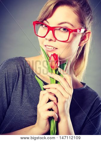 Delicacy and subtlety of women. Young adorable woman with spring flower. Portrait of beauty delicate girl in glasses with red beautiful tulip.