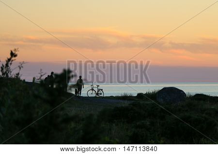 Silhouette of people and bycicle on the beach at sunset.