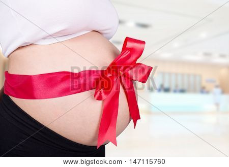 Close Up Pregnant Woman With Red Ribbon Gift On Belly In Hospital Background