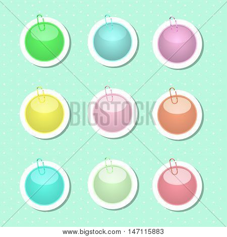 Round paper sticker shapes with paper clips in pastel colors.