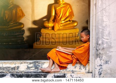 Novice sleeping on the terrace after hard study discipline outside of The Buddha Status. Temple in Thailand.