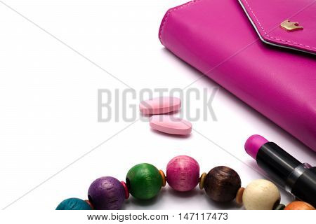Pink vitiamin tablets with magenta purse lip stick and necklace on white background. Women health concept.