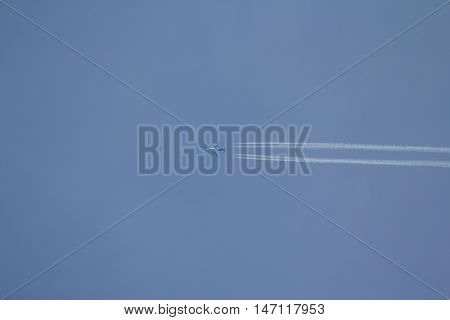 Airplane in the blue sky with condensation trail
