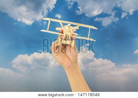 Hand holding wooden airplane model in the sky