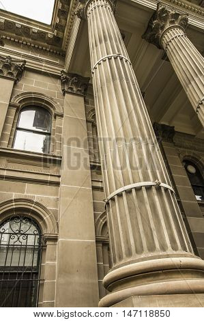 Historical large yellow sandstone building with Roman columns