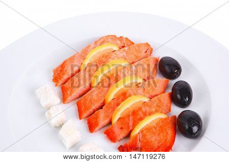 fresh roast wild pink salmon meat fillet with greek goat cheese black olives and raw lemon slices on plate isolated over white background