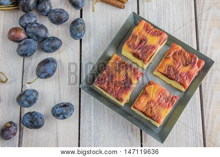 Top View On Plum Cake With Cinnamon On Small Baking Tray On White Table