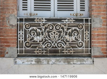 Window with blue shutters and ornate wrought iron window box or balcony on old brick building in Toulouse, France.