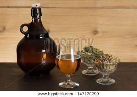 Goblet of beer, growler, hops and malts