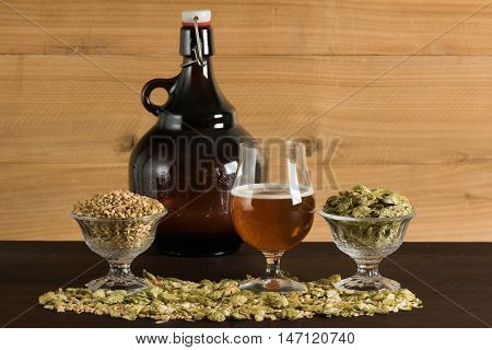 A goblet of beer, with growler, hops and malts