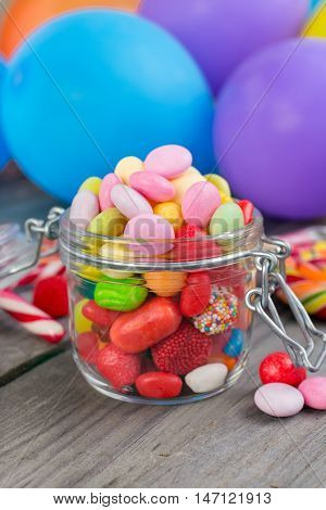 Candy in a glass jar on wooden table close up