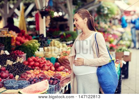 sale, shopping, pregnancy and people concept - happy pregnant woman choosing food at street market