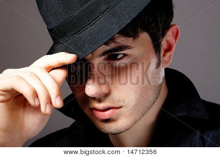 Young man wearing a hat over dark background