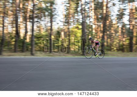 Dynamic sportive girl rides a bike on the road on the nature background. She wears black-pink sportswear, a black helmet, sunglasses and green sneakers. Shoot from the side. Horizontal.