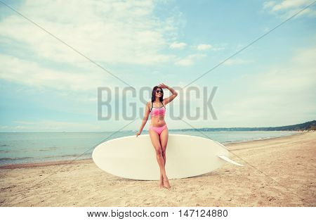 vacation, surfing, water sport and people concept - young woman in swimsuit with surfboard, windsurf or paddle board on summer beach