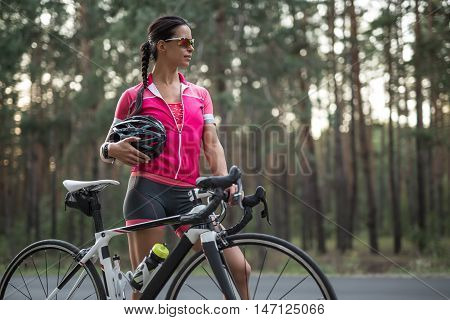 Young girl stands with a bike on the road on the blurry background of nature. She wears pink sports jacket, black-pink shorts, sunglasses and a stopwatch. Woman holds a black helmet in the right hand.