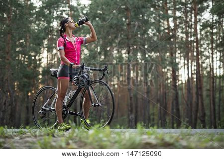 Charming female cyclist stands with a bike on the country road and drinks from the flask in the left hand. She wears pink sports jacket, black-pink shorts, sunglasses, green sneakers and a stopwatch.