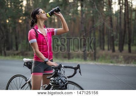 Gorgeous female cyclist stands with a bike on the country road and drinks from the flask in the left hand. She wears pink sports jacket, black-pink shorts, sunglasses and a stopwatch. Horizontal.