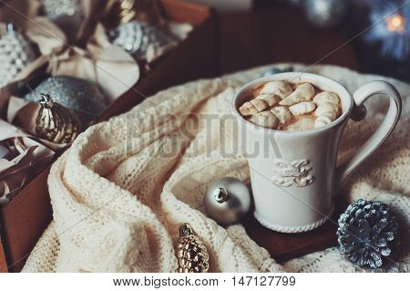 cup of hot cocoa with marshmallow with Christmas decorations at home Christmas tree on background cozy mood