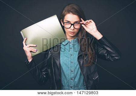 Beautiful young girl. Glasses, denim overalls, a black leather jacket. Woman with folders. Sexy girl. Trendy toning image.