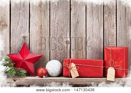 Christmas gift boxes and decor in front of wooden wall. View with copy space for your text