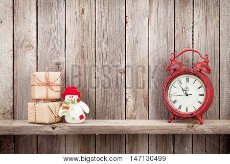 Christmas gift boxes, alarm clock and snowman toy in front of wooden wall. View with copy space