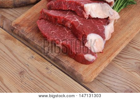 fresh raw beef meat steak and chunk with red hot pepper and dill on wooden cut plates over table