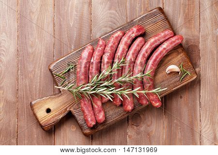 Raw sausages and ingredients for cooking. Top view on wooden table