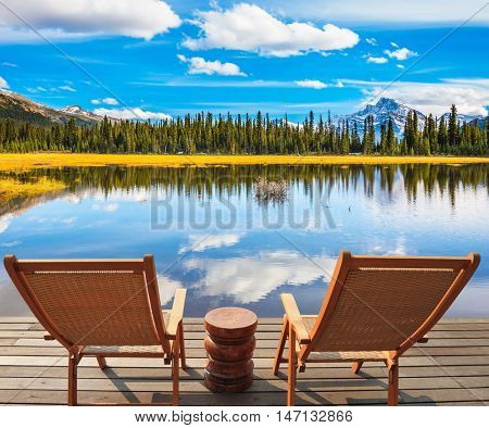 The beautiful nature in northern Rocky Mountains of Canada.  Two comfortable chaise longue in swampy valley. The concept of active and eco-tourism