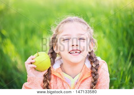 Sweet girl with a fallen tooth holding an apple in her hand on nature