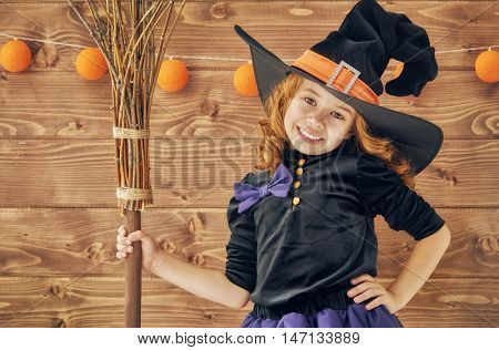 Happy Halloween! Cute little witch with a broomstick.
