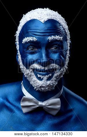 Man painted in blue color with snowy hair and beard grimacing on black background