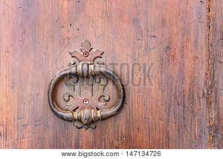 old handle with knocker of a wooden door